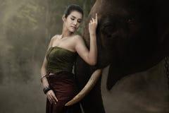 Thailändische Frau im traditionellen Kostüm mit Elefanten Lizenzfreies Stockbild