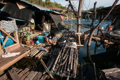Thailändische Frau waschen sie Kleidung auf einem hölzernen Flossfluß stockbild
