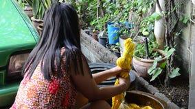 Thailändische Frauen binden den Batik, der gelbe natürliche Farbe färbt stock video