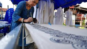 Thailändische Frauen schaffen und Batik, zu malen und zu zeichnen auf Gewebe lassend stock video