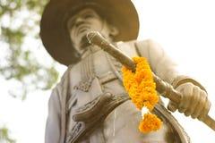 Thailändische Königstatue mit Ringelblume auf Klinge Stockfotografie