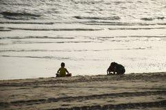 Thailändische Kinder, die Sand auf dem Strand mit Welle und Meer am Verbot spielen Stockfotografie