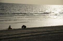 Thailändische Kinder, die Sand auf dem Strand mit Welle und Meer am Verbot spielen stockbild