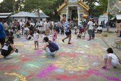 Thailändische Kinder und Elternteilreise- und -spielmalerei pulverisieren Farbe auf dem Boden Lizenzfreie Stockbilder