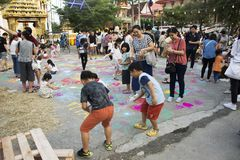 Thailändische Kinder und Elternteilreise- und -spielmalerei pulverisieren Farbe auf dem Boden Stockfoto