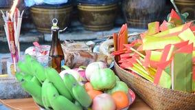 Thailändische Leute bereiten vor sich und Opfer-Angebotlebensmittel auf Holztisch für setzend, beten Sie zum Gott stock footage