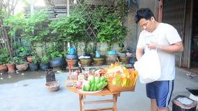 Thailändische Leute bereiten vor sich und Opfer-Angebotlebensmittel auf Holztisch für setzend, beten Sie zum Gott stock video footage