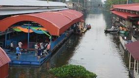 Thailändische Leute beten und legen Nahrung und Sachenangebote Mönchprozession in Boot vor stock footage
