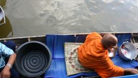 Thailändische Leute beten und legen Nahrung und Sachenangebote Mönchprozession in Boot vor stock video footage