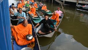 Thailändische Leute beten und legen Nahrung und Sachenangebote Mönchprozession in Boot vor stock video