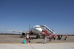 Thail?ndische Leute und foreinger Reisende, die auf Rollbahn nach flacher Landung an internationalem Flughafen Udon Thani in Thai stockfotos