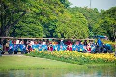 Thailändische Leute und Touristen reiten die Straßentrambetrachtung um den königlichen Garten Rama 9 Stockfotografie