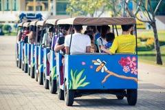Thailändische Leute und Touristen reiten die Straßentrambetrachtung um den königlichen Garten Rama 9 Lizenzfreie Stockbilder