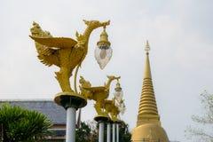 Thailändische Literaturschwäne des Bronzegusses, welche die glockenförmige Stromlaterne gemalt mit Goldfarbe tragen stockfoto