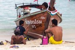 Thailändische Männer, die ein longtail Boot malen stockfoto