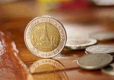 Thailändische Münzen des Stands auf hölzerner Tabelle Stockfoto
