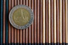 Thailändische Münzenbezeichnung ist eine 10-Baht-Lüge auf der hölzernen Bambustabelle, die für Hintergrund oder Postkarte gut ist Stockfotografie