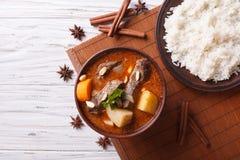 Thailändische Rindfleisch massaman Curry- und Reisbeilage horizontale Draufsicht Stockbild