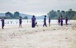 Thailändische Schulkinder, die am Strand spielen Lizenzfreie Stockfotos