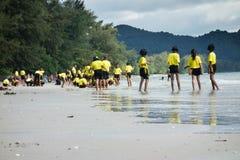 Thailändische Schulkinder, die am Strand spielen Stockbild
