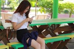 Thailändische Studentin-Hochschulschönes Mädchen, das ihr intelligentes Telefon verwendet Lizenzfreie Stockbilder