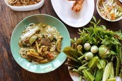 Thailändische Suppennudeln gegessen und Hühnercurry-thailändisches Traditions-Lebensmittel mit Bestandteilen und Kräutern auf höl lizenzfreie stockfotografie