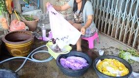 Thailändische waschende Frauen und saubere Kleidung nachdem dem Bindungsbatikfärben stock footage