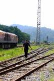 Thailändischer allgemeiner Zug und Railwayman am Bahnhof in Thailand Lizenzfreie Stockfotos