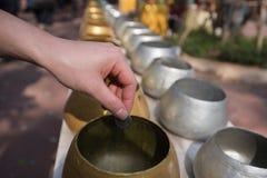 Thailändischer Buddhist spenden Münze in der Schüssel des Mönchs Stockbild