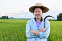 Thailändischer Frauenlandwirt mit Sichel in der Hand Stockfotografie