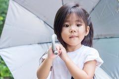 Thailändischer Mädchengriffregenschirm stockbild