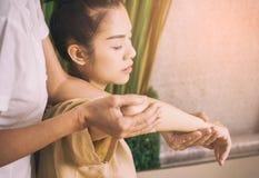 Thailändischer Masseur, der eine Massage auf einem Frauenarm gibt stockbild