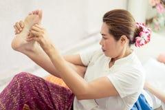 Thailändischer Masseur, der einen Frauenfuß und -bein im thailändischen Massagebadekurort ausdehnt stockfoto