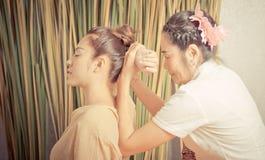 Thailändischer Masseur, der einen Frauenrückseitenarm im thailändischen Massagebadekurort ausdehnt stockbild