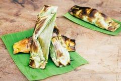 Thailändischer Nachtisch des Konfekts, schwarzer klebriger Reis mit Kokosmilch und babana, Grilled füllten den Klebreis an, der i Stockfotos