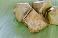 Thailändischer Nachtisch, klebriger Reis mit dem gedämpften Vanillepudding, eingewickelt in Banan stockbilder