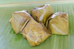 Thailändischer Nachtisch, klebriger Reis mit dem gedämpften Vanillepudding, eingewickelt in Banan stockbild