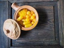 Thailändischer Nachtisch, thailändische Süßspeise in der Tonwarenschüssel auf braunem hölzernem Hintergrund Stockfoto