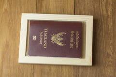Thailändischer Pass- und Holzrahmen auf hölzernem Hintergrund Lizenzfreie Stockbilder