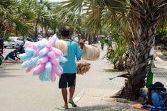 Thailändischer Straßenhändler, der Brot und Zuckerwatte auf einer Straße verkauft Gehender Straßenverkäuferkerl mit vielen Lebens Lizenzfreie Stockbilder