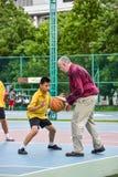 Thailändischer Student übt Basketball mit einem Trainer öffentlich cou Lizenzfreies Stockbild