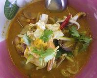 Thailändischer Teller ist die gelben Reisnudeln, die mit Tom Yum-Suppe überstiegen werden, die i stockbilder