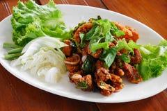 Thailändischer würziger roter Tilapiasalat mit Gemüse auf weißer Platte Stockbilder