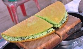 Thailändischer Wannenkuchen, backen Mehl in einem Metall der runden Form durch Holzkohlenofen Stockfoto