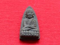 Thailändisches Amulett, auf rotem Hintergrund Stockbild
