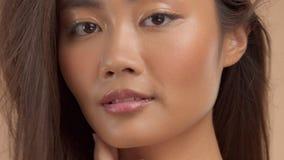 Thailändisches asiatisches Modell mit natürlichem Make-up auf beige Hintergrund stock footage