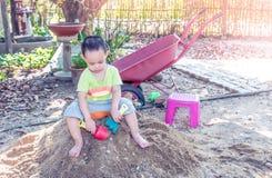 Thailändisches Baby, das auf Sandhaufen mit Spielzeug palying ist Stockfoto