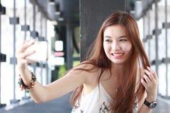 Thailändisches erwachsenes schönes Mädchen, das ihr intelligentes Telefon Selfie verwendet Stockfotos