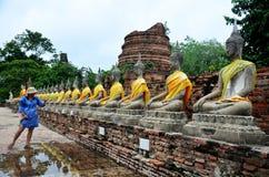 Thailändisches Frauenabnutzung mauhom kleidet Porträt mit Buddha-Statue Stockfotografie