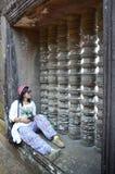 Thailändisches Frauensitzen und machen Foto auf Fenster von Wat Phu oder von Bottich pH Lizenzfreie Stockfotografie